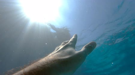 sos : Arm asking for help and trying to reach to the sun. Point of view of man drowning in the sea or ocean and floating to the surface. Male hand stretches from under the water to sunrays. Slow motion POV