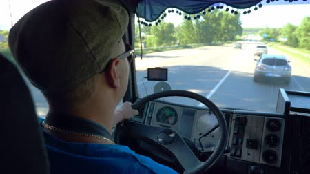 řidič : Unrecognizable lorry driver riding on county road at sunny day. Man in cap and sunglasses controlling his truck attentive watching road. View of traffic from inside cabin. Inside shot Slow mo Close up Dostupné videozáznamy