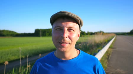 férfias : Portrait of adult smiling man standing with meadow at background. Carefree guy in hat looking into camera with narrowed eyes from sun. Close up of glad emotions on male face. Slow motion Stock mozgókép