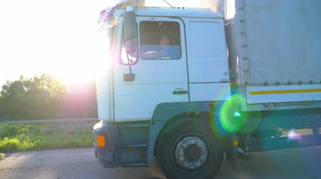pulling up : Truck with cargo trailer driving on highway and transporting goods. White lorry riding to destination through countryside road at sunny day. Bright sun shining at background. Side view Slow motion Stock Footage