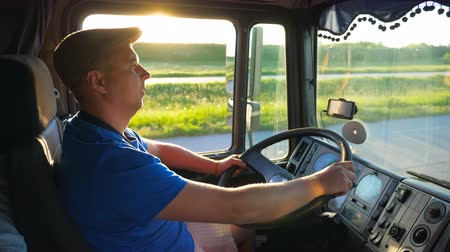 trucks : Profile of lorry driver riding through countryside at sunset time. Man in hat controlling his truck and enjoying journey. Beautiful landscape with bright sunlight at background. Slow motion Close up