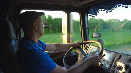 ciężarówka : Profile of lorry driver riding through countryside in evening. Man in hat controlling his truck and enjoying journey. View inside cabin of car. Transport of logistic concept. Slow motion Close up Wideo