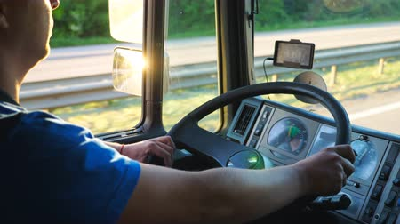 trucks : Unrecognizable man sitting behind wheel of his truck and driving through countryside. Driver holding his hands on big steering wheel and controlling car riding to destination. Slow motion Close up