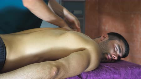masszőr : Professional massagist doing health rubdown of back to athlete in parlor. Muscular sportsman lying on massage table and male hands of masseur slowly massaging him shoulders in salon. Side view Slow mo