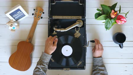 flat lay : Top view on male hands turning on vintage gramophone at white table background. Arm of man putting stylus with needle on rotating black vinyl record to enjoy classical music. Slow motion Close up Stock Footage