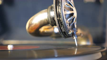 gramophone : Detail view on stylus with needle sliding smoothly on black vinyl record spinning at vintage turntable. Close up of playing gramophone. Blurred background. Retro concept. Slow motion