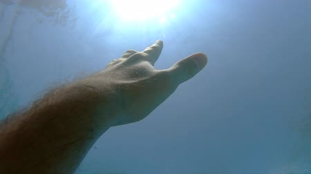 ölen : Male hand stretches from under the water to sunrays. Arm asking for help and trying to reach to the sun. Point of view of man drowning in the sea or ocean and floating to the surface. Slow motion POV Stok Video