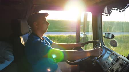 semi profile : Profile of lorry driver riding through countryside at sunset time. Man in hat controlling his truck and enjoying journey. Beautiful landscape with bright sunlight at background. Slow motion Close up