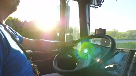 trucks : Lorry driver riding through countryside at sunset time. Man controlling his truck driving to destination. Close up steering wheel and dashboard of car. View inside lorry cab. Side view Slow motion