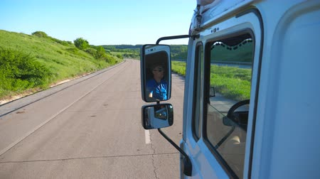 odrážející : Trucker in sunglasses reflecting in side mirror of moving car. Man driving lorry riding to destination through countryside road. Cargo transportation concept. Beautiful background. Slow mo Close up