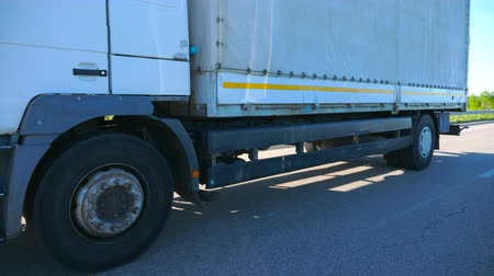 pulling up : Camera follows to truck with cargo trailer driving on highway and transporting goods at summer day. Lorry riding through country with beautiful landscape at background. Slow mo Side view Close up Stock Footage
