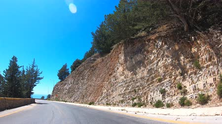 yol kenarı : Point of view of car driving on mountain road with curves and tunnel. Auto ride on serpentine route at sunny summer day. Beautiful landscape with rocks at background. Travel concept. Timelapse POV Stok Video