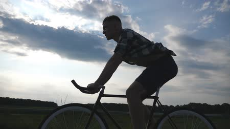 bisikletçi : Silhouette of young man riding at vintage bicycle with beautiful sunset sky at background. Sporty guy cycling in the country road. Male cyclist riding fixed gear bike. Active lifestyle Slow motion Stok Video