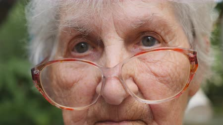 moudrý : Old woman in glasses looking into camera outdoor. Portrait of sad grandmother with emotions and feelings. Granny wearing eyeglasses outside. Close up Slow motion