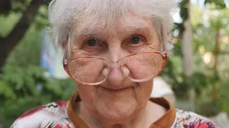 moudrý : Old woman in eyeglasses looking into camera and smiling outdoor. Portrait of happy granny in glasses spending time outside. Emotions of grandmother. Close up Slow motion