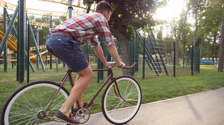bisikletçi : Young handsome man riding a vintage bicycle at amusement park. Sporty guy cycling outdoor. Sun shine at background. Healthy active lifestyle. Close up Slow motion