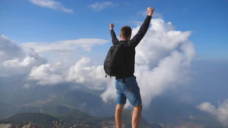 uzanmış : Young male hiker reaching up top of mountain and raising arms. Man enjoying freedom during summer travel. Cloudy sky at background. Rear back view Slow motion