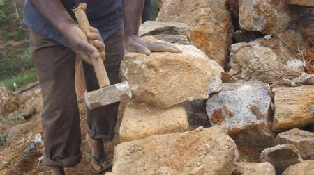 kőműves : Side view of unrecognizable indian man cutting a block of granite with hammer in botanical garden. Adult human hitting stone with sledgehammer for construction flowerbed. Stonemason carving. Close up