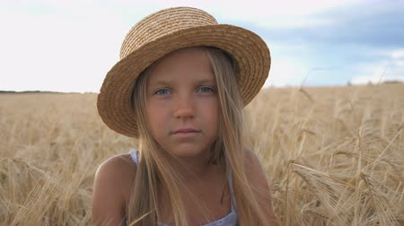 stonky : Portrait of little girl in straw hat looking into camera against the background of wheat field at organic farm. Beautiful small child with blonde hair sitting in the barley meadow. Close up