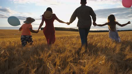 özgürlük : Happy family with two children holding hands of each other and running through wheat field at sunset. Young couple of parents with kids jogging among barley meadow and enjoying nature together