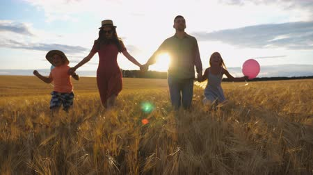 palloncini : Young mother and father with kids holding hands of each other and jogging among barley meadow at sunset. Happy family with two children running through wheat field and enjoying nature together
