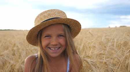 strohoed : Portrait of happy laughing kid with blonde hair in the wheat meadow. Beautiful smiling girl in straw hat looking into camera against the background of barley field at organic farm. Close up