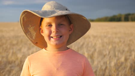 freckles : Handsome smiling boy looking into camera against the blurred background of barley field at organic farm. Portrait of happy laughing kid with freckles standing in the wheat meadow. Close up Slow motion Stock Footage