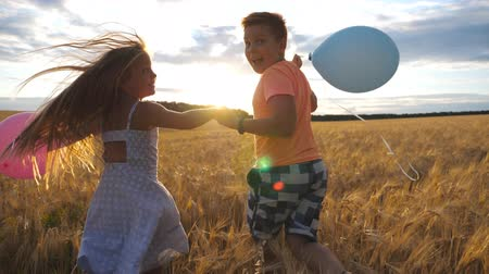 balões : Couple of little kids with balloons running through wheat field, turning to camera and smiling. Small girl and boy holding hands of each other and jogging among barley meadow. Concept of child love