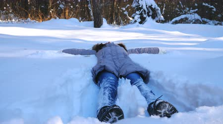 kâr : Unrecognizable young girl lying on snowy meadow and making angel. Happy woman playing in snow enjoying winter time. Cheerful lady having fun outdoor. Concept of winter holiday. Slow motion Close up