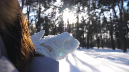 hófúvás : Unrecognizable woman in a white gloves blowing off snow from her palms. Young brunette girl standing among winter forest and playing with snow at sunny day. Blurred background. Slow motion Close up Stock mozgókép