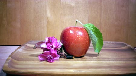 red ripe apple and crimson apple tree flowers on wooden background
