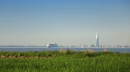 View of the modern districts of St. Petersburg with skyscrapers and bridges and the ships leaving portthrough the Gulf of Finland in summer sunny day Time lapse .
