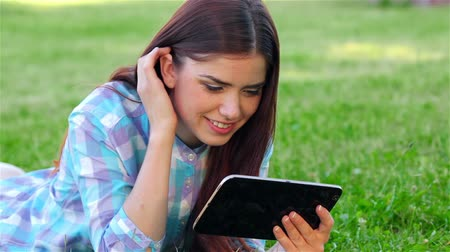 serene : Young beautiful smiling girl with tablet pc, outdoors in the park