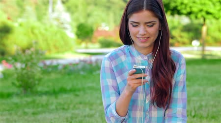 estilo livre : Beautiful girl in park with her phone listens music Vídeos