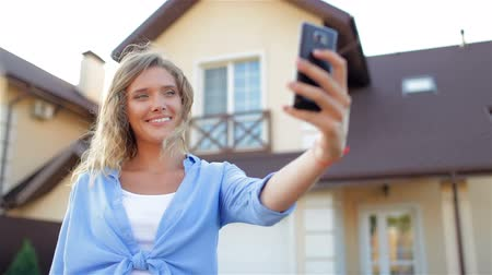 yards : Happy girl talking on the phone, taking selfie. New house Stock Footage