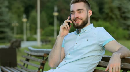 борода : Smiling handsome man talking on the phone in park