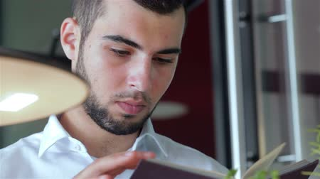 olvasás : Young man in cafe reading a book