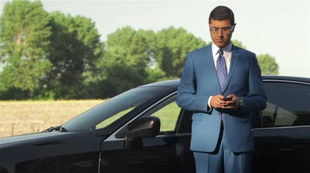 executivo : Young businessman calling on the phone next to car Vídeos