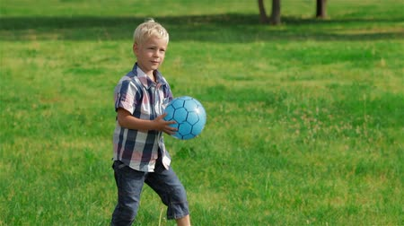 preschool : Elementary aged boy kicking ball in the field
