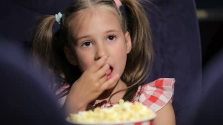 premiere : Beautiful little girl waching movie in the cinema Stock Footage