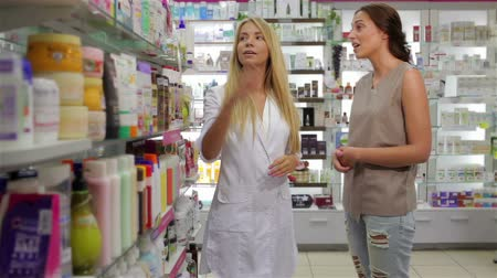 Beautiful girl pharmacist consulting a customer