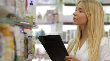фармацевт : Beautiful pharmacist accounting the product in drugstore Стоковые видеозаписи