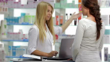 фармацевт : Beautiful girl pharmacist consulting a customer