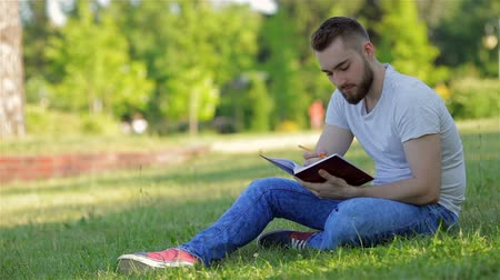 релаксация : Young man sitting in the park with his diary. Leisure time Стоковые видеозаписи