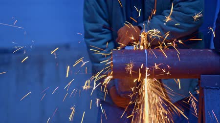 iron pipe : worker cuts the part of the pipe with grinder