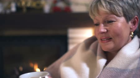 cobertor : Close up of wrapped in a blanket beautiful mature woman drinking coffee on the background of fireplace. Vídeos