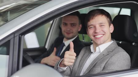 revendedor : Two smiling guys showing thumbs up in the car
