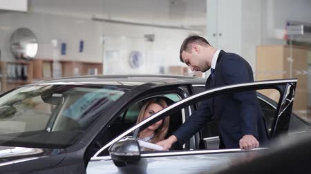 аренда : Salesman explains to girl car specifications in the car dealership