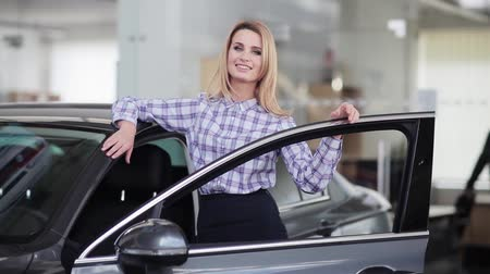 sprzedawca : Beautiful woman posing to camera behind her new car