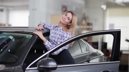 revendedor : Attractive woman hugging her new car